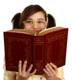 girl with glasses reading a big book